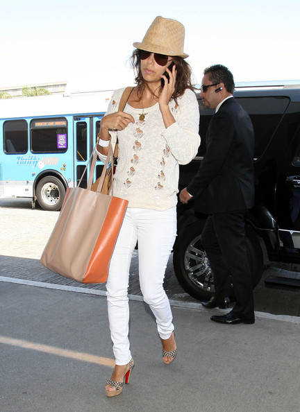Eva Longoria carries a Céline Cabas Tote Bag and wears a pari of Henry & Belle jeans, Stylestalker Macaroon sweater, Christian Louboutin sandals, and enameled Hermès Clic-Clac H bracelet.